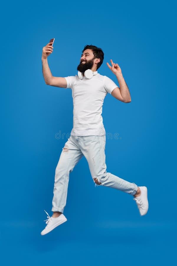Γενειοφόρο άτομο που πηδά και που παίρνει selfie στοκ φωτογραφίες