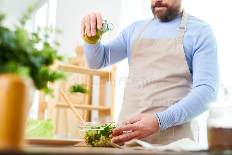 Γενειοφόρο άτομο που προετοιμάζει τη φυτική σαλάτα στοκ εικόνες