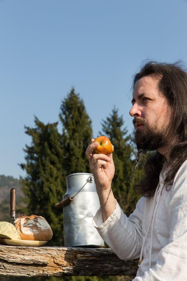 Γενειοφόρο άτομο που τρώει ένα μήλο στη φύση στοκ φωτογραφία με δικαίωμα ελεύθερης χρήσης