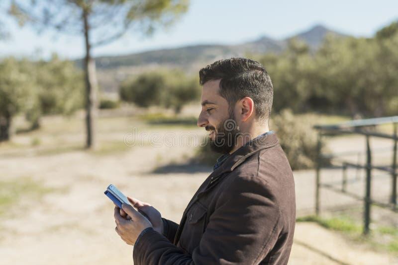 Γενειοφόρο άτομο που φαίνεται smartphone στοκ εικόνες