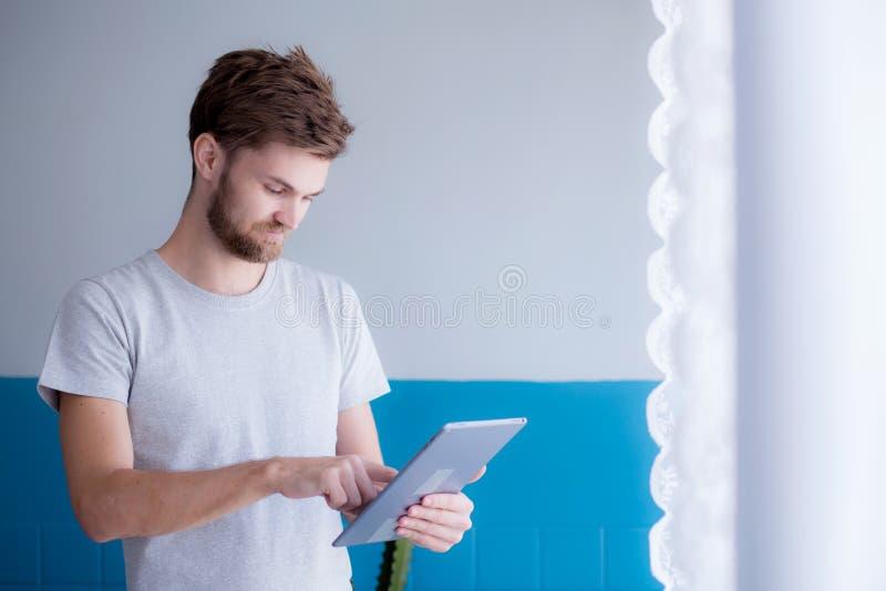 Γενειοφόρο άτομο που χρησιμοποιεί την ταμπλέτα στεμένος κοντά στο παράθυρο στο σύγχρονο διαμέρισμά του στοκ φωτογραφία