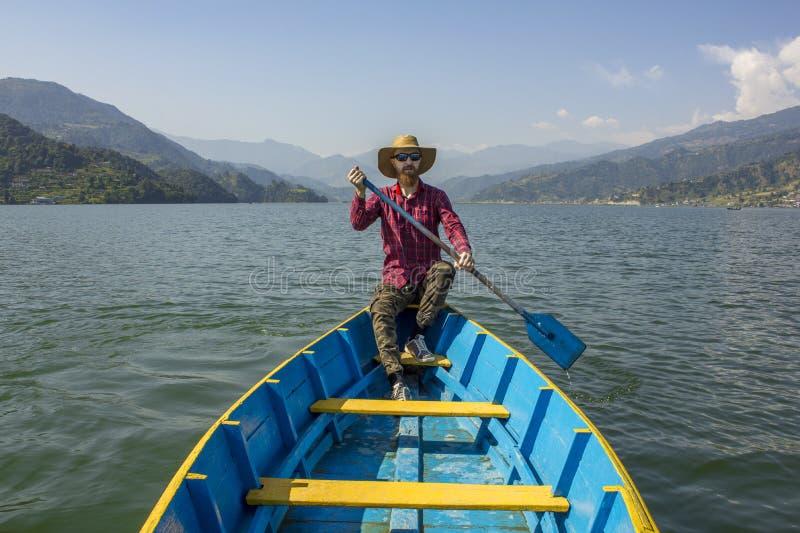 Γενειοφόρο άτομο σε ένα κόκκινο πουκάμισο, ένα καπέλο και τα γυαλιά ηλίου σε μια μπλε ξύλινη βάρκα με ένα κουπί στα χέρια του, στ στοκ φωτογραφία
