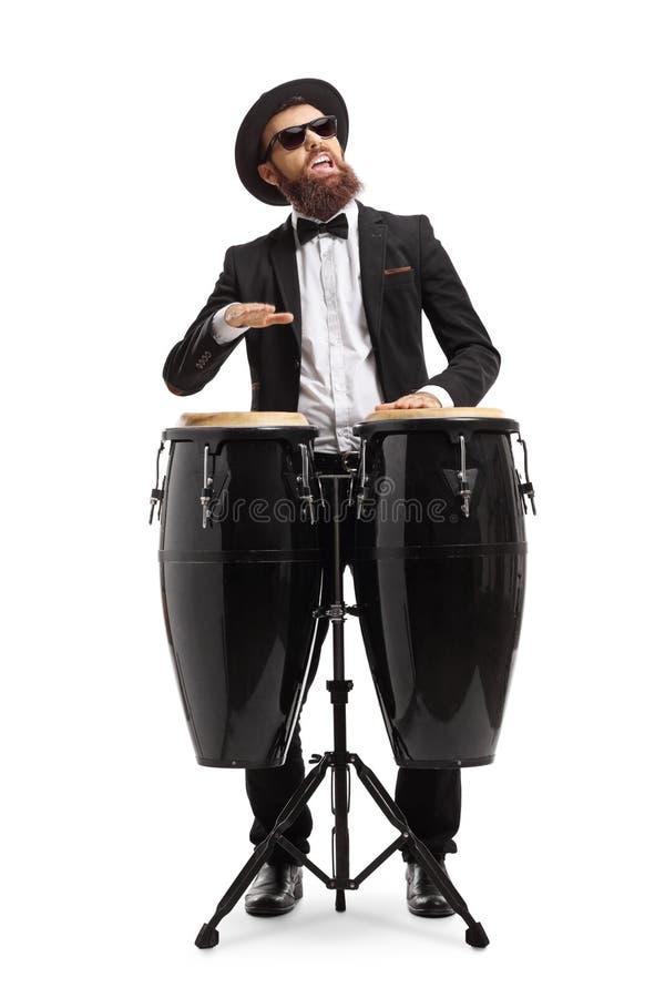 Γενειοφόρο άτομο στα τύμπανα ενός κοστουμιών παιχνιδιού conga στοκ εικόνα με δικαίωμα ελεύθερης χρήσης