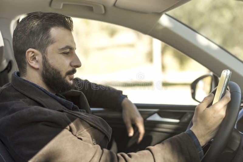 Γενειοφόρο άτομο στο αυτοκίνητό του που φαίνεται smartphone στοκ φωτογραφίες με δικαίωμα ελεύθερης χρήσης