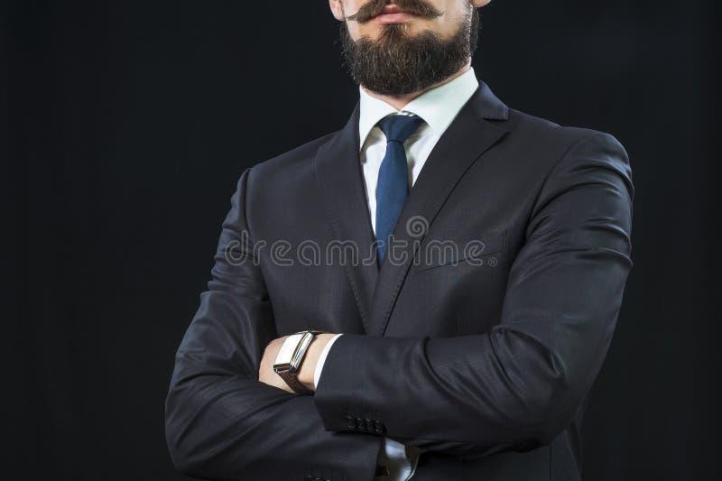 Γενειοφόρο άτομο στο κοστούμι που διασχίζει τα όπλα του στο στήθος στοκ εικόνες
