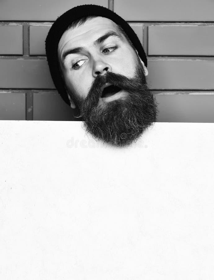 Γενειοφόρο βάναυσο καυκάσιο hipster με το φύλλο της Λευκής Βίβλου στοκ φωτογραφία με δικαίωμα ελεύθερης χρήσης