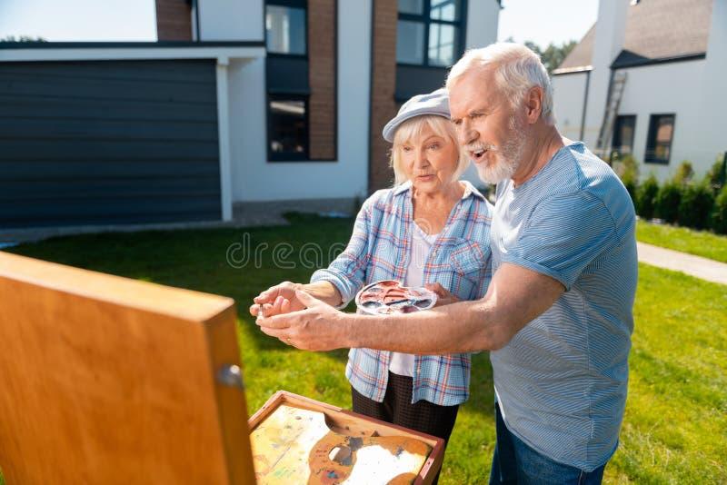 Γενειοφόρο ηλικιωμένο άτομο που παίρνει τη βούρτσα ζωγραφικής βοηθώντας τη φύση σχεδίων συζύγων του στοκ εικόνα
