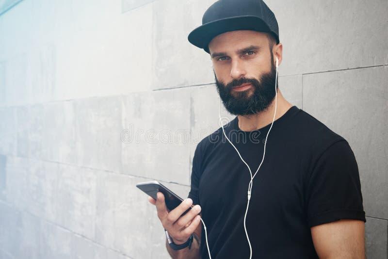 Γενειοφόρο μυϊκό άτομο που φορά το μαύρο θερινό χρόνο Snapback ΚΑΠ μπλουζών κενό Νεαροί άνδρες που χαμογελούν απέναντι από το κεν στοκ φωτογραφία με δικαίωμα ελεύθερης χρήσης
