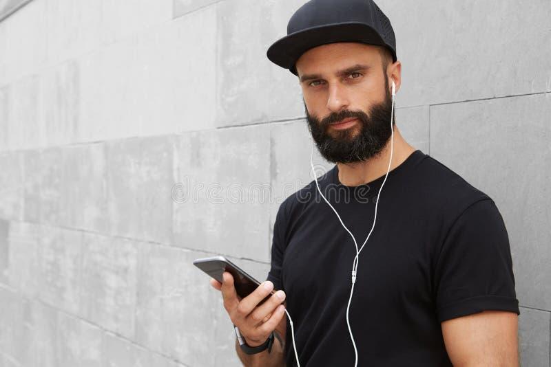 Γενειοφόρο μυϊκό άτομο που φορά το μαύρο θερινό χρόνο Snapback ΚΑΠ μπλουζών κενό Νεαροί άνδρες που χαμογελούν απέναντι από το κεν στοκ εικόνες