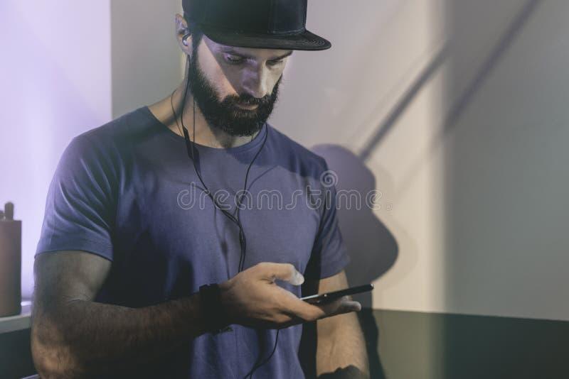 Γενειοφόρο μυϊκό άτομο που φορά το μαύρο snapback ΚΑΠ που στέκεται στον καφέ με τα ακουστικά Άτομα που χρησιμοποιούν το κινητό τη στοκ εικόνα