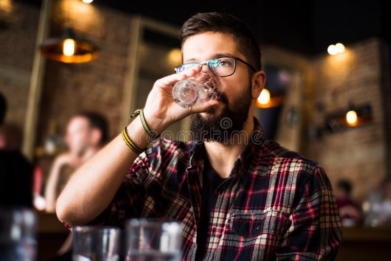 Γενειοφόρο πόσιμο νερό ατόμων σε έναν φραγμό καφέ στοκ εικόνα