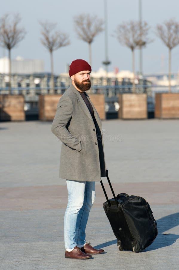 Γενειοφόρο ταξίδι hipster ατόμων με τη μεγάλη τσάντα αποσκευών στις ρόδες Αφήστε το ταξίδι να αρχίσει Ταξιδιώτης με την αναμονή β στοκ φωτογραφία
