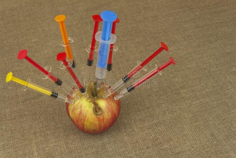 Γενετική έννοια τροποποίησης Φρούτα και syginge Apple που λαμβάνει μια έγχυση κάποιας ουσίας για τη γρήγορη ωρίμανση στοκ εικόνες
