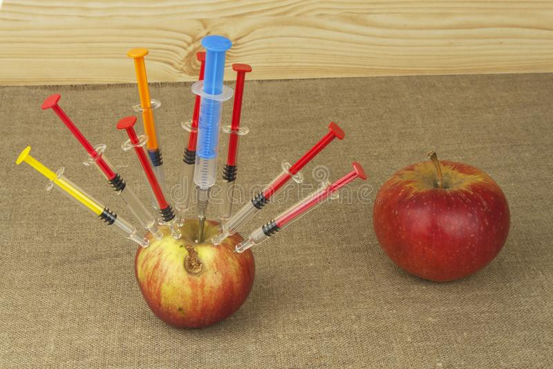 Γενετική έννοια τροποποίησης Φρούτα και syginge Apple που λαμβάνει μια έγχυση κάποιας ουσίας για τη γρήγορη ωρίμανση στοκ φωτογραφίες