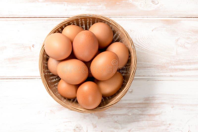 Γενικά έξοδα των καφετιών αυγών κοτόπουλου στον ψάθινο δίσκο στοκ φωτογραφία