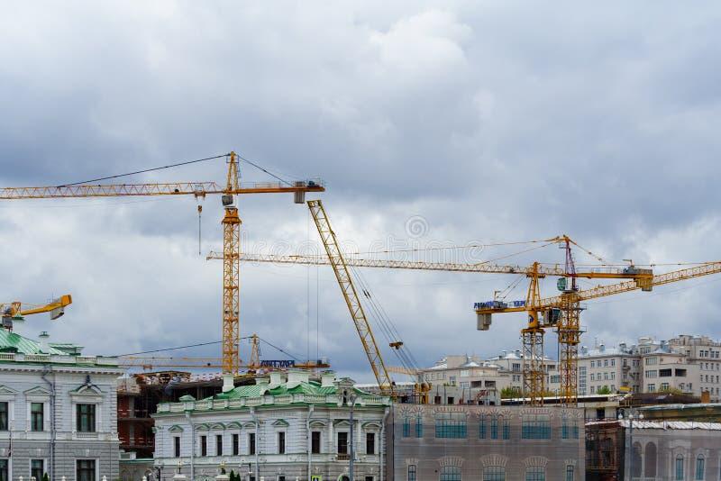 Γενική άποψη σχετικά με τους γερανούς πύργων στο κέντρο πόλεων ενάντια σε ένα γκρίζο συννεφιάζω κύριο άρθρο ουρανού στοκ φωτογραφίες