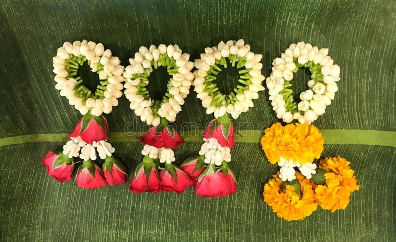 Γενική γιρλάντα λουλουδιών στα πράσινα φύλλα μπανανών στοκ εικόνες