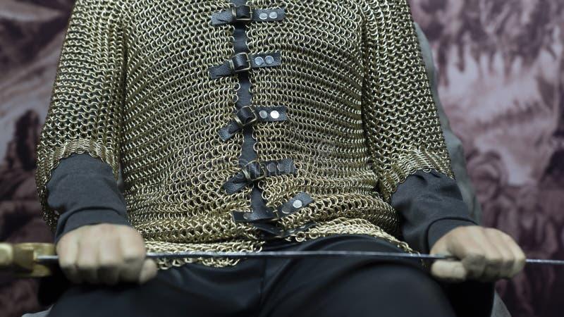 Γενναίος πολεμιστής που κρατά το ξίφος και την ασπίδα του και που κάθεται στο θρόνο στοκ φωτογραφίες με δικαίωμα ελεύθερης χρήσης