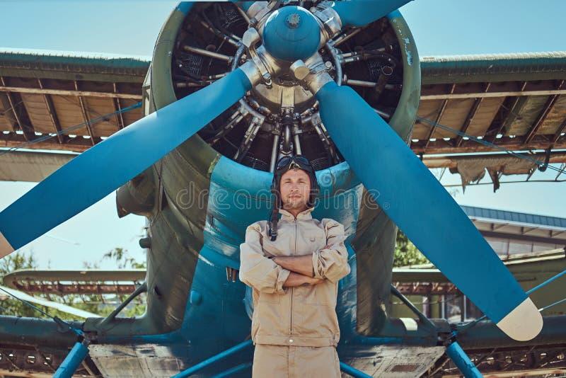 Γενναίος όμορφος πειραματικός σε ένα πλήρες εργαλείο πτήσης που στέκεται με τα διασχισμένα όπλα κοντά στο στρατιωτικό αεροπλάνο στοκ εικόνες