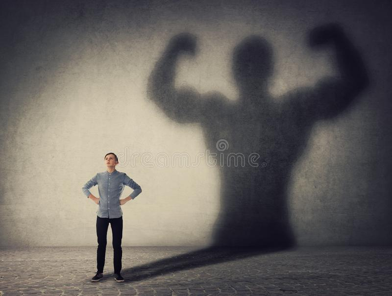 Γενναίο έφηβο αγόρι που αντιμετωπίζει τους φόβους του ως ισχυρός ήρωας Τύπος που ρίχνει μια δυνατή μυϊκή σκιά αμαξώματος, δείχνον στοκ φωτογραφίες