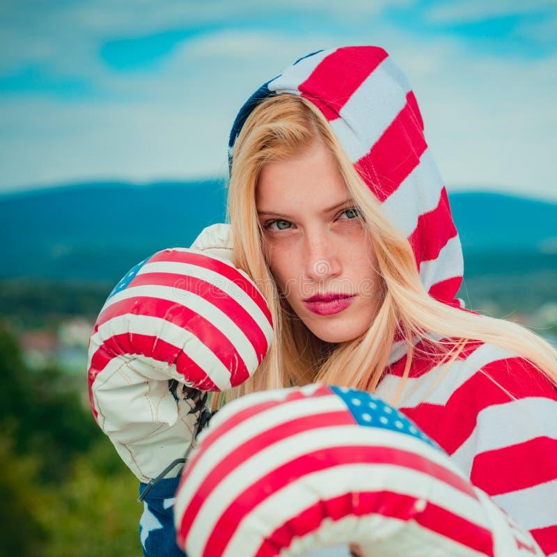 Γενναίο αμερικανικό ενήλικο κορίτσι πατριωτών σε έναν 4ο του Ιουλίου Κλείστε τη γυναίκα μπόξερ σηκώνεται έτοιμος να χτυπήσει, φορ στοκ εικόνα με δικαίωμα ελεύθερης χρήσης