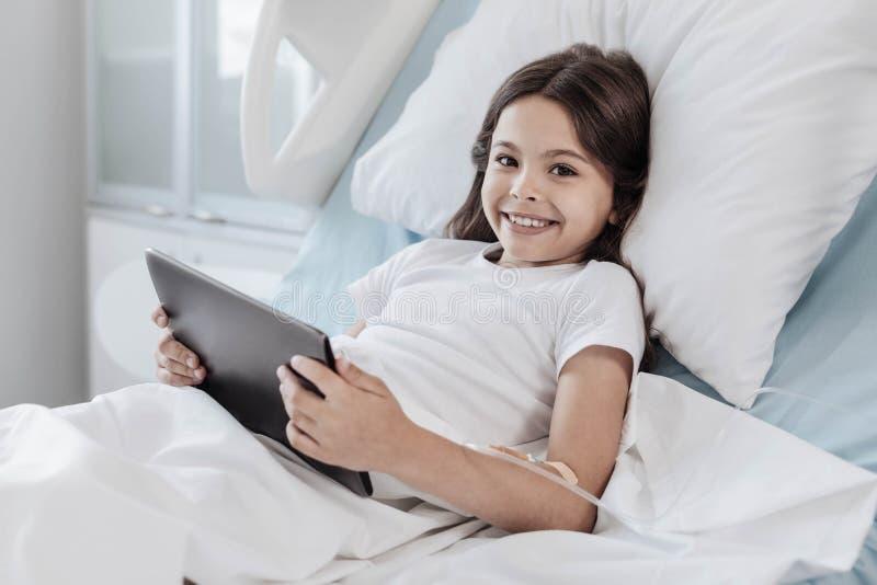 Γενναίο παιχνίδι κοριτσιών στο touchpad στο νοσοκομειακό κρεβάτι στοκ φωτογραφία με δικαίωμα ελεύθερης χρήσης