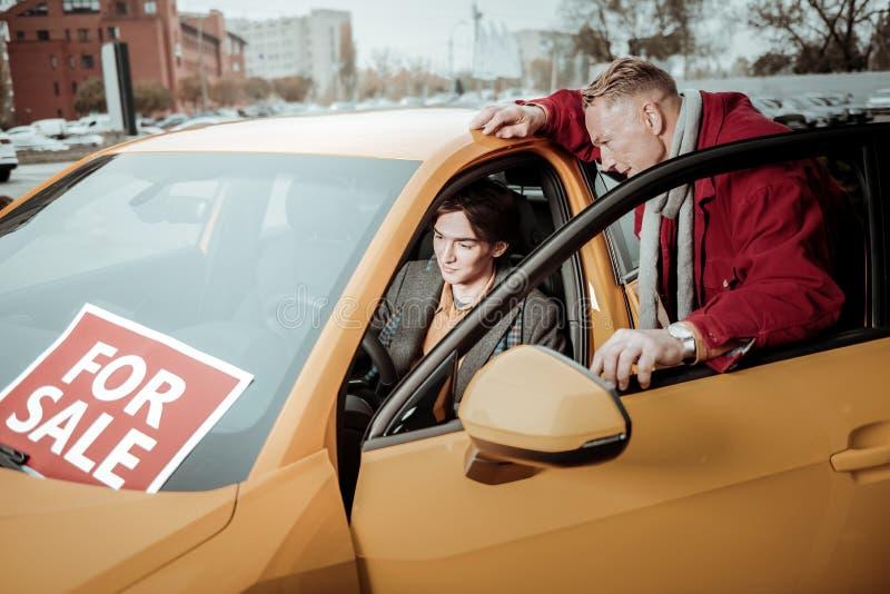 Γενναιόδωρος αγαπώντας πατέρας που αγοράζει το νέο επιβατικό αυτοκίνητο για το γιο στοκ εικόνες με δικαίωμα ελεύθερης χρήσης
