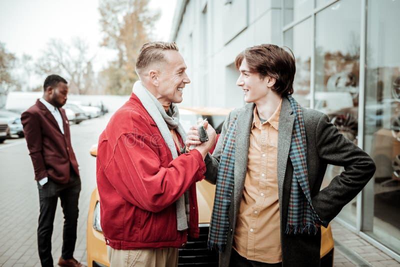 Γενναιόδωρος αγαπώντας πατέρας που παρουσιάζει τα νέα κλειδιά αυτοκινήτων γιων του στοκ φωτογραφία