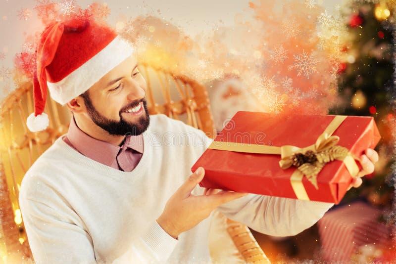Γενναιόδωρος ευγενικός φίλος που κρατά το συμπαθητικό μεγάλο κιβώτιο δώρων Χριστουγέννων για τη σύζυγό του στοκ εικόνες