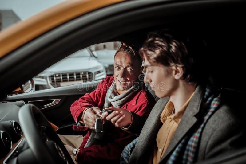 Γενναιόδωρο συναίσθημα πατέρων συγκινημένο παρουσίαση των κλειδιών αυτοκινήτων στο γιο του στοκ εικόνα με δικαίωμα ελεύθερης χρήσης
