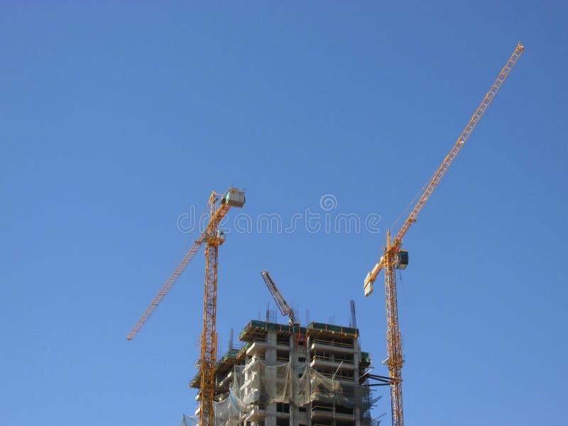 Γερανοί και under-construction πολυκατοικία ενάντια στο μπλε ουρανό στοκ φωτογραφίες