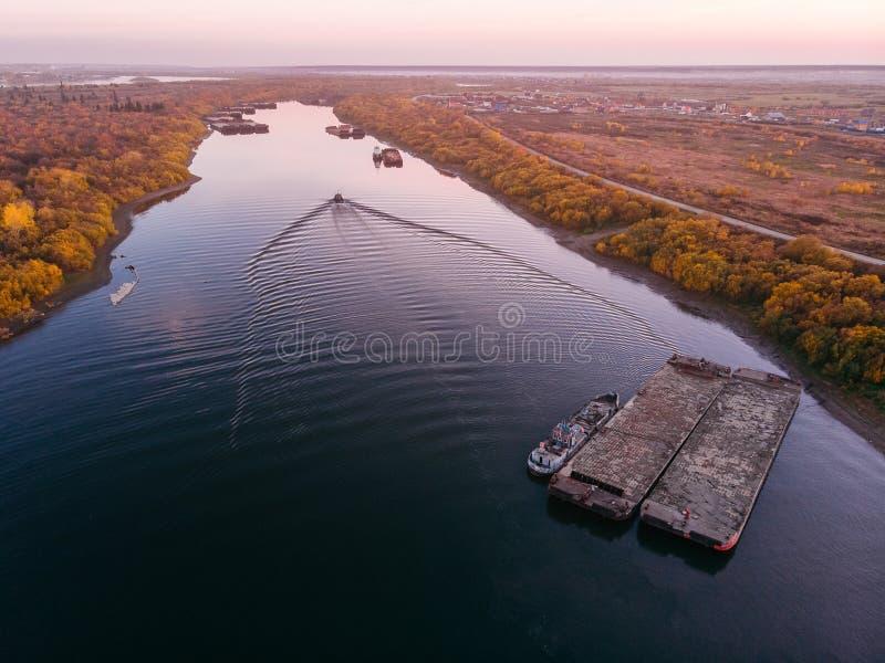 Γερανοί ποταμών λιμένων που φορτώνουν τα σκάφη στην παράδοση φορτηγίδων, ηλιοβασίλεμα στοκ φωτογραφία