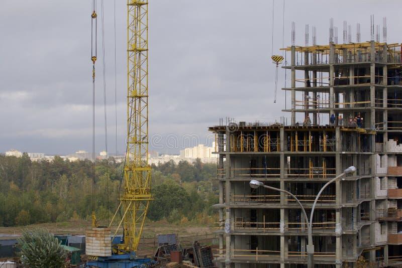 Γερανοί πύργων στην οικοδόμηση ενός κτηρίου με ένα πλαίσιο του ενισχυμένου σκυροδέματος Ηλιοφώτιστος ενάντια σε έναν μπλε ουρανό στοκ εικόνες