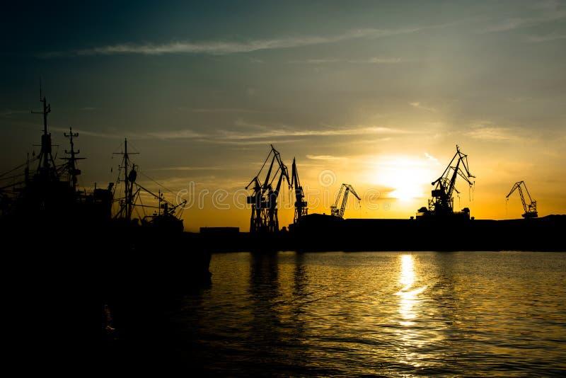 Γερανοί στο ηλιοβασίλεμα στο λιμάνι Pula στην Κροατία στοκ εικόνα