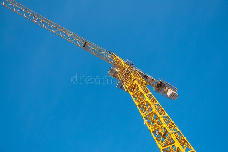 Γερανός κατασκευής ενάντια στο μπλε ουρανό με τα σύννεφα στοκ εικόνα
