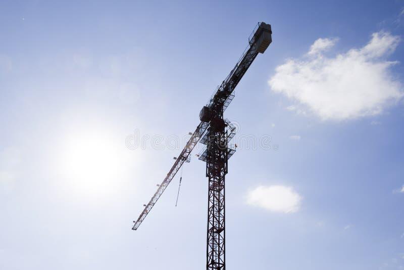 Γερανός οικοδόμησης πύργων ενάντια στο μπλε ουρανό και τον ήλιο σπίτι κατασκευής νέο Οικοδόμηση των νέων κτηρίων με έναν γερανό Π στοκ εικόνα