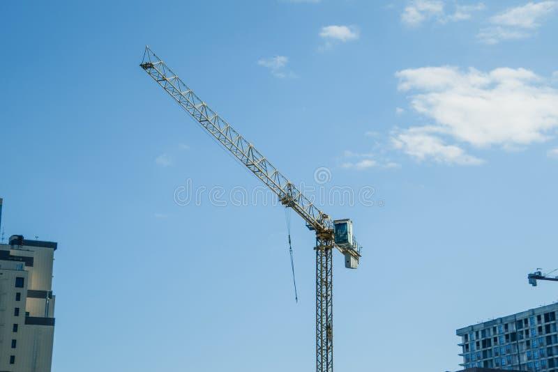 Γερανός οικοδόμησης πύργων ενάντια στο μπλε ουρανό και τον ήλιο Οικοδόμηση των νέων κτηρίων με έναν γερανό πύργος γερανών στοκ φωτογραφία