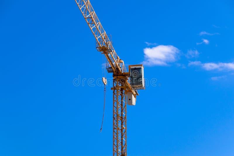 Γερανός οικοδόμησης πύργων ενάντια στο μπλε ουρανό και τον ήλιο Οικοδόμηση των νέων κτηρίων με έναν γερανό πύργος γερανών στοκ εικόνες με δικαίωμα ελεύθερης χρήσης
