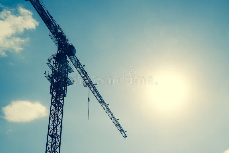 Γερανός οικοδόμησης πύργων ενάντια στο μπλε ουρανό και τον ήλιο Οικοδόμηση των νέων κτηρίων με έναν γερανό πύργος γερανών στοκ εικόνα