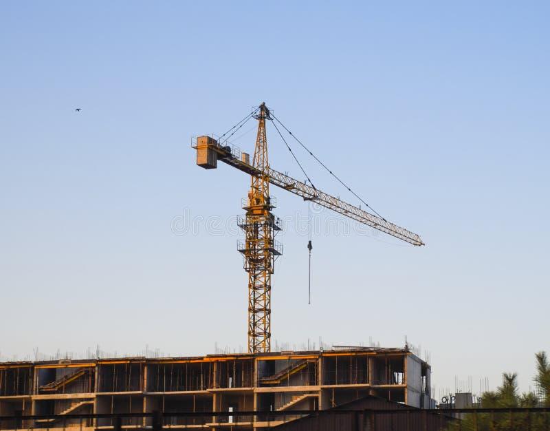 Γερανός οικοδόμησης πύργων κοντά στο καινούργιο σπίτι κάτω από την κατασκευή στοκ εικόνες