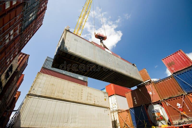 Γερανός που χαμηλώνει το εμπορευματοκιβώτιο στο σωρό των εμπορευματοκιβωτίων στοκ φωτογραφία