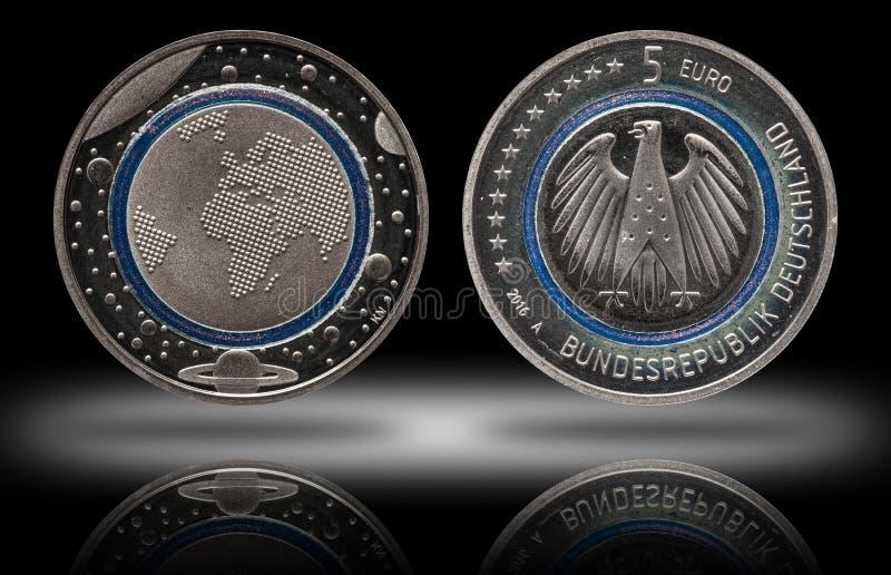 Γερμανία πέντε ευρο- νόμισμα με τους πλανήτες και το μπλε πολυμερές δαχτυλίδι στοκ εικόνες