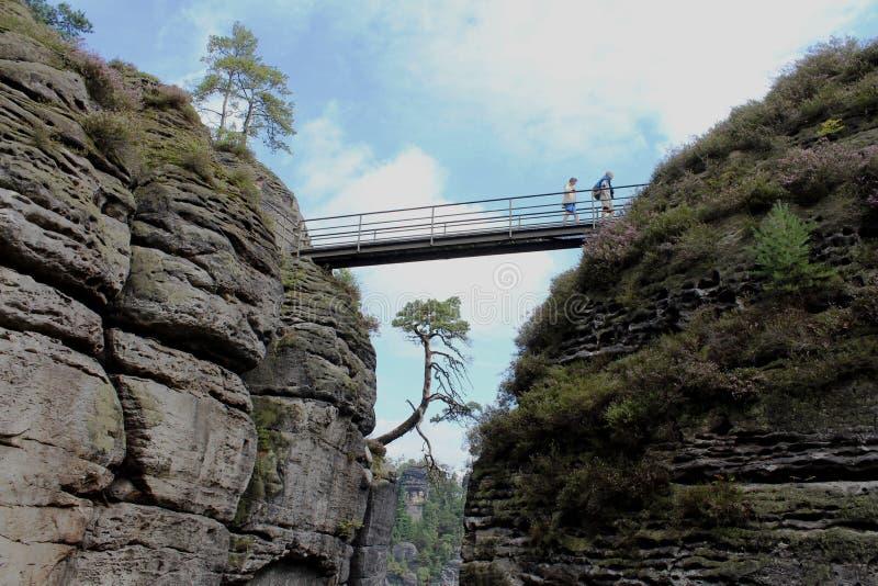 Γερμανία, Σαξωνία: Οι άνθρωποι περπατούν κατά μήκος της γέφυρας μεταξύ των βουνών στοκ φωτογραφία με δικαίωμα ελεύθερης χρήσης