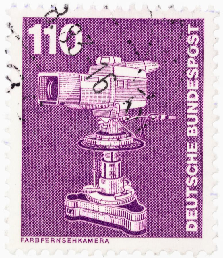 ΓΕΡΜΑΝΙΑ - CIRCA 1982: Ένα γραμματόσημο που τυπώνεται στη Γερμανία παρουσιάζει τηλεοπτική κάμερα χρώματος από τη βιομηχανία σειρά στοκ φωτογραφία