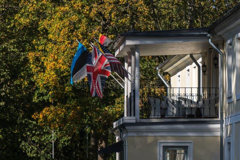 Γερμανικά, βρετανικά, εσθονικά και αμερικανικές σημαίες που κυματίζουν στον αέρα στο παλαιό σπίτι στοκ φωτογραφία με δικαίωμα ελεύθερης χρήσης