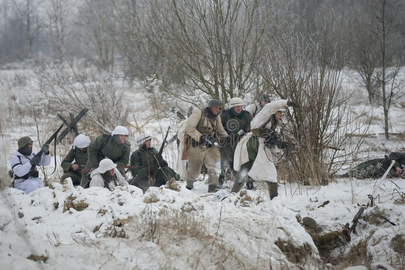 Γερμανικά infantrymen της περιόδου Δεύτερου Παγκόσμιου Πολέμου το νεφελώδες χειμερινό απόγευμα Ένα τεμάχιο στρατιωτικός και ιστορ στοκ εικόνες