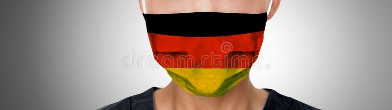 Γερμανική σημαία μασκών COVID- 19 στο γιατρό PPE, που φοράει πανοραμικό πανό μάσκας Πανδημία του Coronavirus στη Γερμανία στοκ εικόνα