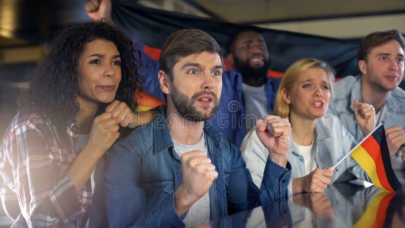 Γερμανικοί οπαδοί ποδοσφαίρου που υποστηρίζουν τη εθνική ομάδα στην αντιστοιχία, που ανησυχεί για τη νίκη στοκ εικόνα με δικαίωμα ελεύθερης χρήσης