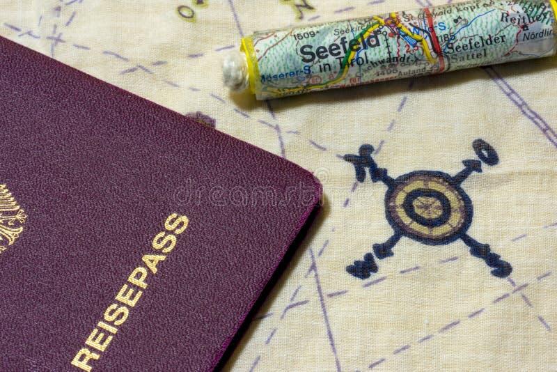 Γερμανικό διαβατήριο και κυλημένος επάνω χάρτης στο διάγραμμα στοκ εικόνες