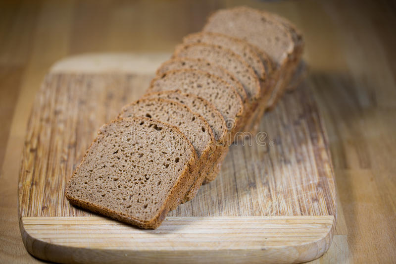 Γερμανικό ψωμί, ολόκληρο σιτάρι στον ξύλινο πίνακα στοκ φωτογραφίες
